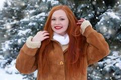 Όμορφη γυναίκα δέντρα χειμερινού στα υπαίθρια, χιονώδη έλατου στη δασική, μακριά κόκκινη τρίχα, που φορά ένα sheepskin παλτό Στοκ Εικόνες