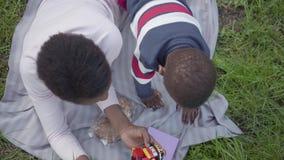 Όμορφη γυναίκα αφροαμερικάνων με την κοντή τρίχα που βρίσκεται στη χλόη στο πάρκο με το γιο της που παίζει με το πλαστικό απόθεμα βίντεο
