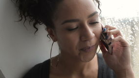 Όμορφη γυναίκα αφροαμερικάνων με το τηλέφωνο κυττάρων φιλμ μικρού μήκους