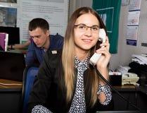 Όμορφη γυναίκα εργαζόμενος γραφείων που μιλά στο τηλέφωνο ρολόι πεννών γραφείων σημειωματάριων έννοιας Στοκ Φωτογραφία