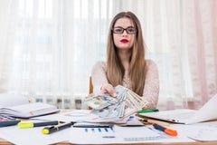 Όμορφη γυναίκα, εργαζόμενος γραφείων, που προσφέρει τα τραπεζογραμμάτια δολαρίων στοκ εικόνα
