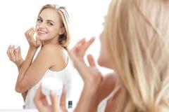 Όμορφη γυναίκα εφαρμόζοντας κάποια του προσώπου κρέμα στη μύτη της στοκ εικόνα