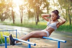 Όμορφη γυναίκα ικανότητας που κάνει την άσκηση ηλιόλουστο σε υπαίθριο φραγμών στοκ εικόνα