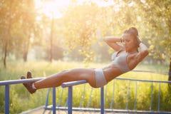 Όμορφη γυναίκα ικανότητας που κάνει την άσκηση ηλιόλουστο σε υπαίθριο φραγμών στοκ εικόνες με δικαίωμα ελεύθερης χρήσης