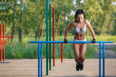 Όμορφη γυναίκα ικανότητας που κάνει την άσκηση παράλληλο ηλιόλουστο σε υπαίθριο φραγμών στοκ εικόνες