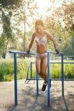 Όμορφη γυναίκα ικανότητας που κάνει την άσκηση παράλληλο ηλιόλουστο σε υπαίθριο φραγμών στοκ εικόνα με δικαίωμα ελεύθερης χρήσης
