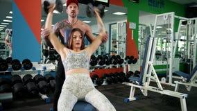 Όμορφη γυναίκα και ένας βάναυσος άνδρας στον ανυψωτικό αλτήρα γυμναστικής Πανέμορφος ανυψωτικός αλτήρας γυναικών με το σύζυγό της απόθεμα βίντεο