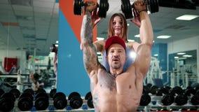 Όμορφη γυναίκα και ένας βάναυσος άνδρας στον ανυψωτικό αλτήρα γυμναστικής Πανέμορφος ανυψωτικός αλτήρας γυναικών με το σύζυγό της φιλμ μικρού μήκους