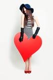 Όμορφη γυναίκα και μεγάλο κόκκινο έμβλημα καρδιών Στοκ εικόνες με δικαίωμα ελεύθερης χρήσης