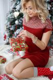 Όμορφη γυναίκα κοντά σε ένα χριστουγεννιάτικο δέντρο με ένα φλιτζάνι του καφέ με marshmallows Στοκ Φωτογραφία
