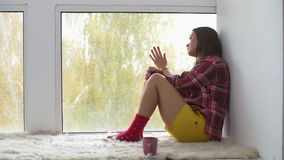 Όμορφη γυναίκα κοντά στο παράθυρο που χάνει τον αγαπημένο άνδρα απόθεμα βίντεο