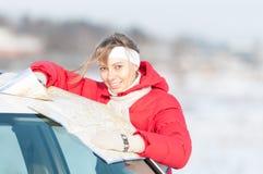 Όμορφη γυναίκα κοντά στο χάρτη εκμετάλλευσης αυτοκινήτων το χειμώνα. Στοκ Εικόνες