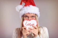 Όμορφη γυναίκα με ένα καπέλο Santa που κρατά ένα κιβώτιο δώρων Στοκ φωτογραφίες με δικαίωμα ελεύθερης χρήσης