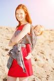 Όμορφη γυναίκα με ένα μωρό σε μια σφεντόνα μωρό mom Μητέρα και Στοκ Εικόνες