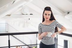 Όμορφη γυναίκα με ένα φλυτζάνι του αρωματικού καφέ που στέκεται επάνω από το κύριο δωμάτιο και που εξετάζει τη κάμερα Στοκ εικόνα με δικαίωμα ελεύθερης χρήσης