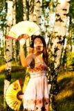 Όμορφη γυναίκα με δύο ανεμιστήρες στον ήλιο στοκ φωτογραφία