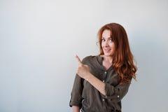 Όμορφη γυναίκα με κόκκινο τρίχας με τα δάχτυλα και να παρουσιάσει μακριά Στοκ φωτογραφία με δικαίωμα ελεύθερης χρήσης