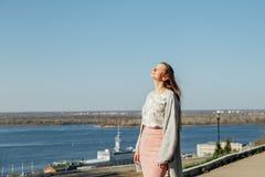 Όμορφη γυναίκα με μακρυμάλλη απολαμβάνοντας τη θέα πόλεων από τη γέφυρα μια ηλιόλουστη ημέρα στοκ εικόνες