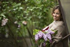 όμορφη γυναίκα με μια ανθοδέσμη των πασχαλιών και ένα βιβλίο στα χέρια του, υπαίθρια μεταξύ της πρασινάδας Στοκ Εικόνες