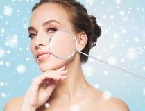 Όμορφη γυναίκα με πιό magnifier στο πρόσωπο πέρα από το χιόνι Στοκ Φωτογραφίες