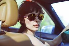 Όμορφη γυναίκα με τα γυαλιά πίσω από τη ρόδα Στοκ φωτογραφία με δικαίωμα ελεύθερης χρήσης