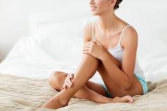 Όμορφη γυναίκα με τα γυμνά πόδια στο κρεβάτι στο σπίτι Στοκ φωτογραφία με δικαίωμα ελεύθερης χρήσης