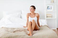 Όμορφη γυναίκα με τα γυμνά πόδια στο κρεβάτι στο σπίτι Στοκ φωτογραφίες με δικαίωμα ελεύθερης χρήσης