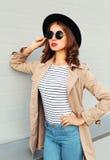 Όμορφη γυναίκα με τα κόκκινα χείλια που φορούν το παλτό γυαλιών ηλίου μαύρων καπέλων μόδας πέρα από το γκρι Στοκ φωτογραφία με δικαίωμα ελεύθερης χρήσης