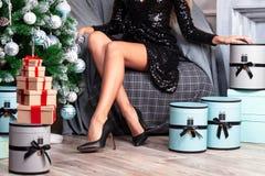 Όμορφη γυναίκα με τα μακριά λεπτά πόδια στο προκλητικό μαύρο φόρεμα στοκ φωτογραφίες