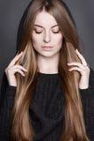 Όμορφη γυναίκα με τα μακριά, πανέμορφα σκοτεινά ξανθά μαλλιά Είναι ντυμένη θερμό σε γκρίζο πλέκει το φόρεμα με μια κουκούλα Στοκ Φωτογραφίες