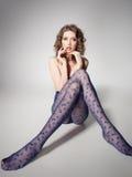 Όμορφη γυναίκα με τα μακριά προκλητικά πόδια που φορούν τις γυναικείες κάλτσες που θέτουν στο στούντιο - πλήρες σώμα Στοκ Εικόνες