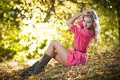 Όμορφη γυναίκα με τα μακριά πόδια στο πάρκο φθινοπώρου Στοκ Φωτογραφίες