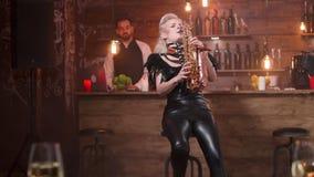 Όμορφη γυναίκα με τα μοντέρνα μαύρα παιχνίδια ενδυμάτων σε ένα saxophone απόθεμα βίντεο