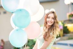 όμορφη γυναίκα με τα πετώντας πολύχρωμα μπαλόνια Στοκ Φωτογραφίες