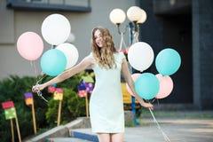 όμορφη γυναίκα με τα πετώντας πολύχρωμα μπαλόνια Στοκ Εικόνες