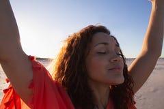 Όμορφη γυναίκα με τα όπλα που στέκονται επάνω στην παραλία στην ηλιοφάνεια στοκ φωτογραφία με δικαίωμα ελεύθερης χρήσης