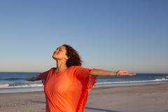 Όμορφη γυναίκα με τα όπλα που τεντώνονται να ξεχωρίσει στην παραλία στην ηλιοφάνεια στοκ εικόνες
