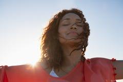Όμορφη γυναίκα με τα όπλα που τεντώνονται να ξεχωρίσει στην παραλία στην ηλιοφάνεια στοκ φωτογραφία με δικαίωμα ελεύθερης χρήσης