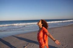Όμορφη γυναίκα με τα όπλα που τεντώνονται να ξεχωρίσει στην παραλία στην ηλιοφάνεια στοκ εικόνες με δικαίωμα ελεύθερης χρήσης