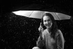 Όμορφη γυναίκα με την ασημένια συνεδρίαση φορεμάτων κάτω από μια ομπρέλα στο ν Στοκ Φωτογραφία