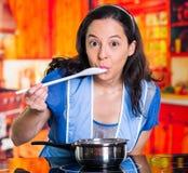 Όμορφη γυναίκα με την μπλε ποδιά που εξετάζει τη γεύση της προετοιμασίας σε ένα δοχείο Στοκ φωτογραφίες με δικαίωμα ελεύθερης χρήσης