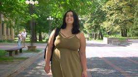 Όμορφη γυναίκα με την παχυσαρκία που χαμογελά και που εξετάζει τη κάμερα, που στέκεται στην οδό στο πάρκο, ευτυχής και εύθυμος απόθεμα βίντεο