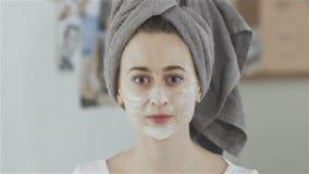 Όμορφη γυναίκα με την πετσέτα στην επικεφαλής βούρτσα χρήσης στην εφαρμογή της καλλυντικής μάσκας φιλμ μικρού μήκους