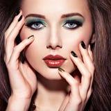 Όμορφη γυναίκα με την πράσινη σύνθεση και τα δημιουργικά καρφιά στοκ εικόνα