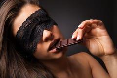 Όμορφη γυναίκα με την προκλητική σοκολάτα κατανάλωσης blindfold Στοκ Φωτογραφίες