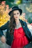 Όμορφη γυναίκα με την τοποθέτηση μαύρων καπέλων στο φθινοπωρινό πάρκο Νέος χρόνος εξόδων brunette κατά τη διάρκεια του φθινοπώρου Στοκ Εικόνες