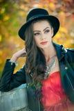 Όμορφη γυναίκα με την τοποθέτηση μαύρων καπέλων στο φθινοπωρινό πάρκο Νέος χρόνος εξόδων brunette κατά τη διάρκεια του φθινοπώρου Στοκ Φωτογραφίες