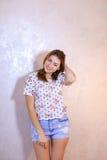 Όμορφη γυναίκα με την τοποθέτηση χαμόγελου στη κάμερα, που στέκεται στο υπόβαθρο Στοκ φωτογραφίες με δικαίωμα ελεύθερης χρήσης