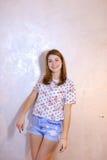 Όμορφη γυναίκα με την τοποθέτηση χαμόγελου στη κάμερα, που στέκεται στο υπόβαθρο Στοκ εικόνα με δικαίωμα ελεύθερης χρήσης