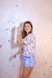 Όμορφη γυναίκα με την τοποθέτηση χαμόγελου στη κάμερα, που στέκεται στο υπόβαθρο Στοκ φωτογραφία με δικαίωμα ελεύθερης χρήσης